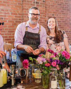 Castle & Key: a man in a purple top with an apron smiling off camera and a woman next to him smiling at the camera
