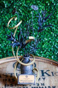 Castle & Key: a trophey sitting on a bourbon barrel with greenery behind it