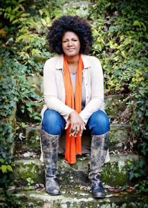 Ouita Michel: woman with a jacket and scarf sitting in nature smiling at the camera