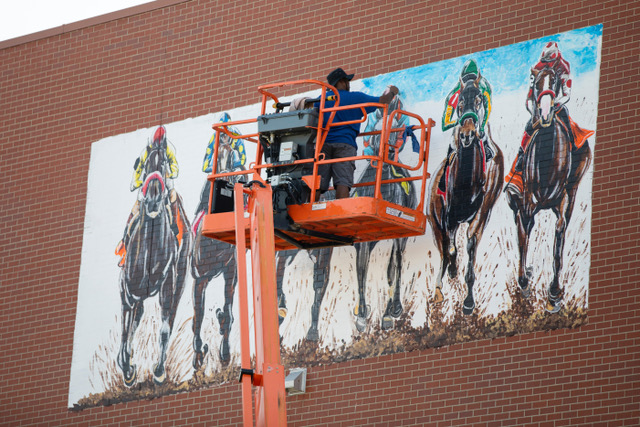 derby: a man painting a mural on a brick building