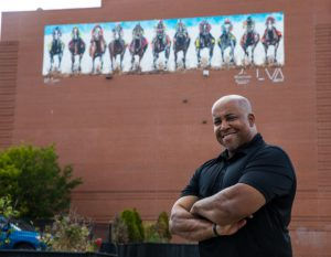 derby: a man posing with a brick building and a mural behind him
