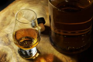 bourbon bar: bourbon in a glass and a bottle on a wooden table