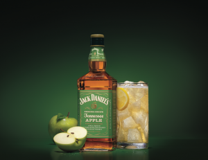 Jack Daniel: bottle with a green lable, a glass, and apple next to it