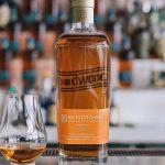 goodwood brewing: bourbon bottle and glass on a bar