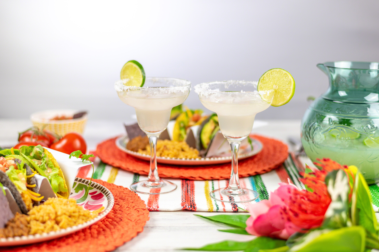Margaritas and Mexican food on colorful tabletop